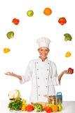 Frauenchef, der mit Frischgemüse jongliert. Getrennt Lizenzfreie Stockbilder