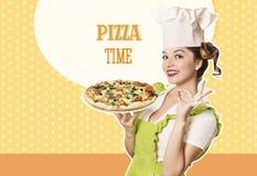 Frauenchef, der Pizza auf Retro- Hintergrund hält Lizenzfreies Stockfoto
