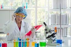 Frauenchemiker ist, messend erfassend und Daten lizenzfreies stockbild