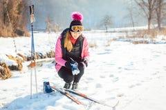 Frauencross country-Skifahrer, der auf Ski sich setzt lizenzfreie stockbilder