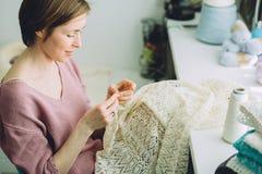 Frauendesigner, der zartes Kleid mit Häkelarbeit strickt Abschluss oben Kreatives Arbeiten des weiblichen Freiberuflers am gemütl lizenzfreies stockbild