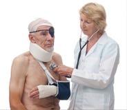 Frauendoktor, der älteren Patienten mit Verletzungen überprüft Stockfotografie