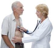 Frauendoktor, der zum Kasten des älteren Mannes hört Lizenzfreie Stockfotos