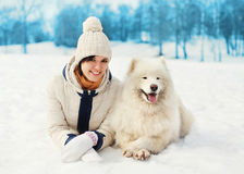 Fraueneigentümer mit dem weißen Samoyedhund, der auf Schnee im Winter liegt Stockbild