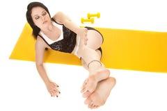Fraueneignungsgelbmattenlage-Beinseite stockfoto