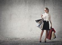 Fraueneinkaufen, das ihr Telefon überprüft Stockbilder