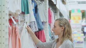 Fraueneinkaufen in einem Bekleidungsgeschäft für Kinder Kind-` s Kleidung auf Aufhängern stock video