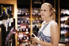 Fraueneinkaufen für Alkohol in einem Flaschenspeicher Lizenzfreies Stockbild