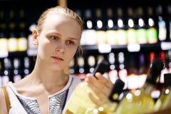 Fraueneinkaufen für Alkohol in einem Flaschenspeicher Stockbilder