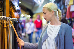 Fraueneinkaufen für neuen Ledergürtel Lizenzfreie Stockbilder