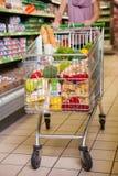 Fraueneinkaufen mit ihrer Laufkatze voll von den Produkten Lizenzfreie Stockfotos