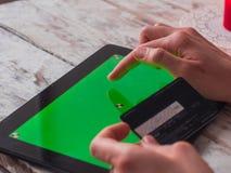 Fraueneinkaufen unter Verwendung des Tabletten-PC und -Kreditkarte Leerer grüner Schirm Lizenzfreies Stockbild