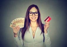 Fraueneinkaufen, welches das Zeigen von Kreditkarte- und Bargeldeurobanknoten hält Lizenzfreies Stockbild