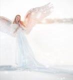 Frauenengel mit Flügeln im Winter Schneeengel, der im Schnee, der Wächter des Winters, ein fabelhaftes Bild steht stockbild