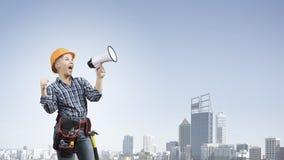 Frauenerbauer mit Megaphon Stockbild
