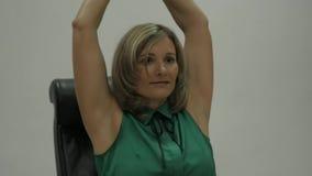 Frauenexekutive, die Übung an ihrem Lehnsessel an Arbeitsplatz ausdehnend tut Langsame Bewegung stock video footage