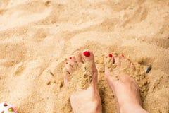 Frauenfüße auf dem Sand Stockfoto