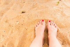 Frauenfüße auf dem Sand Stockbild