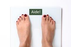 Frauenfüße auf Gewichtsskalen Lizenzfreie Stockbilder