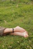 Frauenfüße auf Gras Stockbild