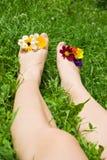 Frauenfüße, die auf dem Gras sich entspannen Lizenzfreies Stockfoto
