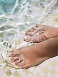 Frauenfüße im Wasser Stockbild