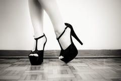 Frauenfüße mit schwarzem Detail der hohen Absätze Stockfotografie