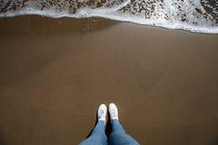 Frauenfüße sehen mit Jeans von oben genanntem am Strand mit Sand und an der Welle, die in den Rahmen kommt an stockfotografie