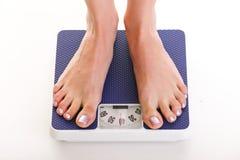 Frauenfüße und Gewichtsskala lokalisiert auf weißem Hintergrund Lizenzfreie Stockfotografie