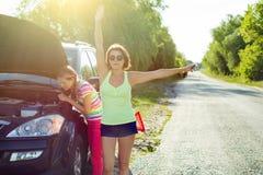 Frauenfahrer mit einem Kind auf einer Landstraße, nahe einem defekten Auto Stockbild