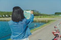 Frauenfahrfahrrad in der kleinen Straße zur Natur während Blick auf Reisekarte lizenzfreie stockfotografie