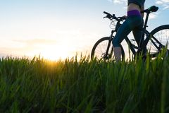 Frauenfahrradsonnenuntergang ?bung bei Sonnenuntergang stockfotos