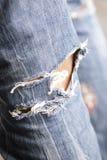 Frauenfahrwerkbein in durchlöcherten Jeans Lizenzfreie Stockbilder