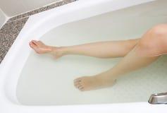 Frauenfahrwerkbeine in der Badewanne Lizenzfreies Stockfoto