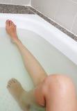 Frauenfahrwerkbeine in der Badewanne Stockfotos
