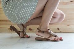 Frauenfahrwerkbeine, die auf Schuhe sich setzen Lizenzfreies Stockbild