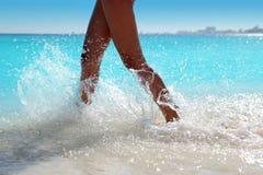 Frauenfahrwerkbeine, die Strandaquawasser spritzend gehen stockfotos