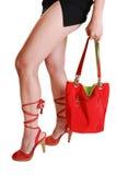 Frauenfahrwerkbeine mit Handtasche. Stockfoto