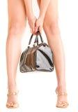 Frauenfahrwerkbeine und eine Handtasche Lizenzfreies Stockfoto
