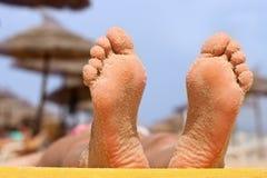Frauenfüße auf dem Strand Stockfoto