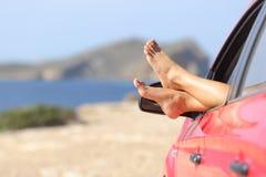 Frauenfüße, die in einem Auto auf dem Strand sich entspannen Stockfotografie