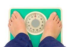 Frauenfüße und Gewichtskala Lizenzfreie Stockfotos