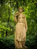 Frauenfigur gemacht vom Stein unter Bäumen lizenzfreie stockfotos