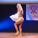 Frauenfigurmodell biegt ihre Muskeln und zeigt ihr Konstitution Lizenzfreies Stockbild