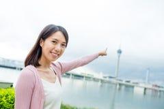Frauenfinger, der auf den Macao-Turm zeigt Lizenzfreie Stockfotografie