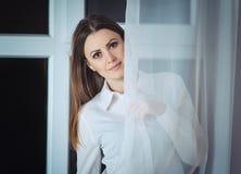 Frauenflüchtiger blick heraus vom Vorhang Stockbild