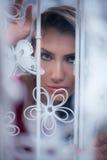 Frauenflüchtiger blick heraus von hinten weißen Vorhang nahe dem Fenster Lizenzfreies Stockbild