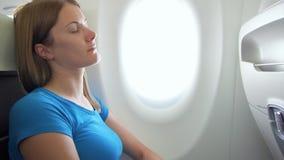 Frauenfliegen im Flugzeug in der Tageszeit Ermüdet durch die Jetlagfrau, die nahe Fenster während der Turbulenz schläft