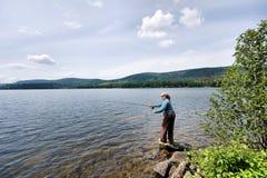 Frauenfliegenfischen weg vom Ufer lizenzfreies stockfoto