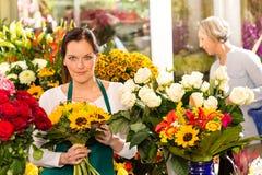Frauenflorist, der Sonnenblumeblumenstrauß-Blumenladen verkauft Lizenzfreies Stockbild
